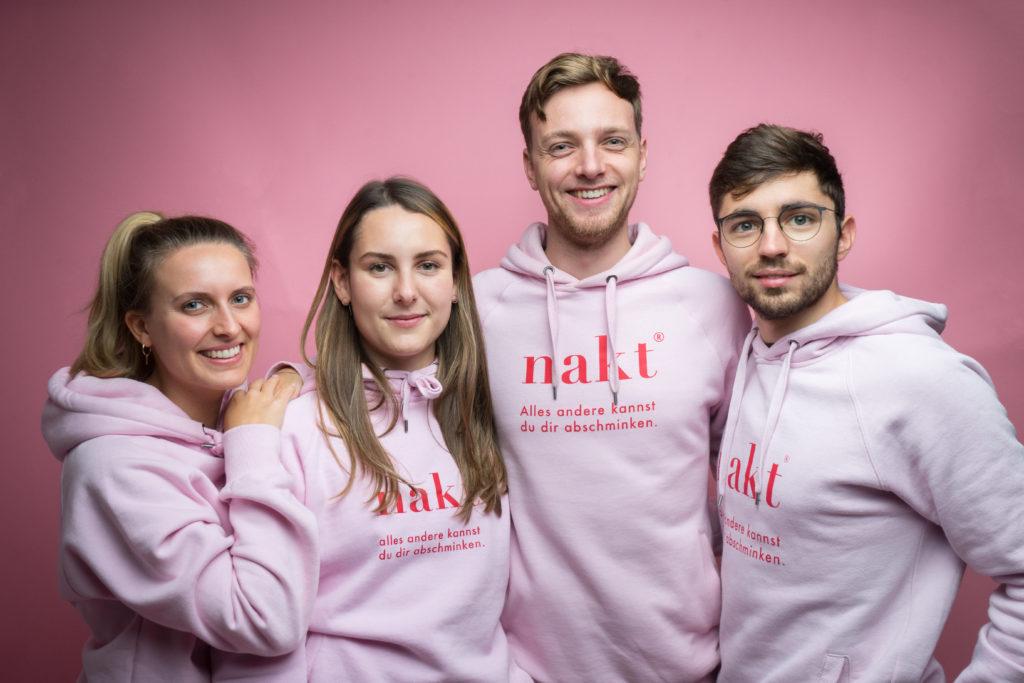 Das Team von nakt® steht in einer Reihe in ihren Firmenpullovern vor einem rosa Hintergrund. Links steht eine blonde junge Frau, daneben Louisa und rechts von ihr zwei junge Männer.