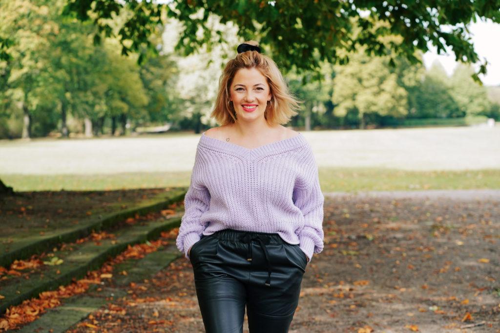 Angelina hat einen violetten Strickpullover und eine schwarze Hose an. Ihre blonden, schulterlangen Haare trägt sie offen. Sie geht lächelnd durch einen Park auf die Kamera zu.