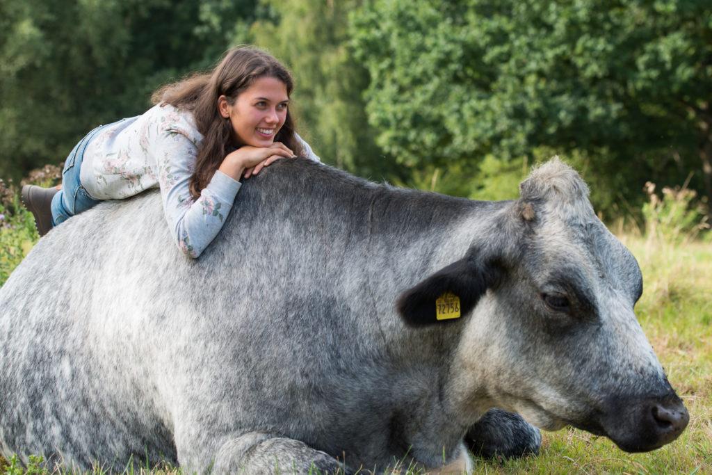 Julie liegt lächelnd auf dem Rücken einer liegenden, grauen Kuh. Julie trägt dunkle Gummiestiefel, eine Jeans und einen grauen Pullover. Ihre braunen langen Haare fallen ihr über die Schulter.