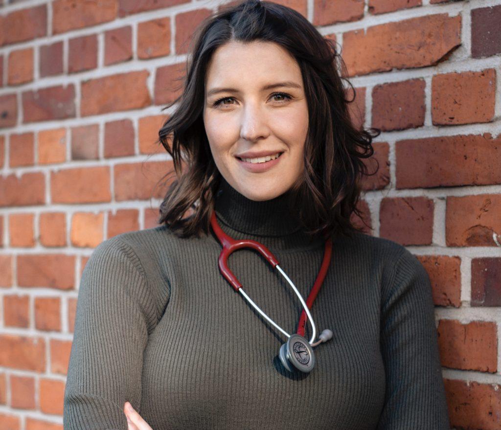 Die brünette Hannah trägt ein dunkelgrünen Rollkragenpullover und hat ein rotes Stetoskop um ihren Hals gelegt. Sie steht vor einer Backsteinwand und kuckt freundlich in die Kamera