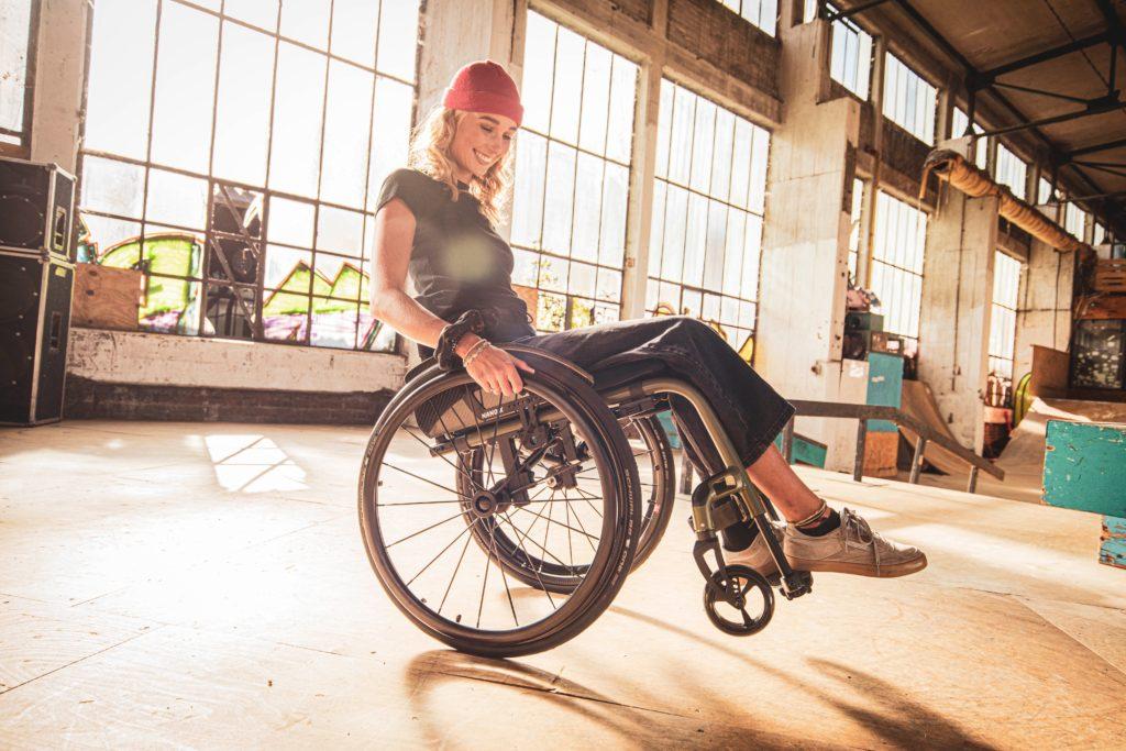 Elena trägt eine rote Mütze auf ihren offenen blonden Haaren. Sie sitzt in ihrem Rollstuhl in einer Industriehalle. Hinter ihr scheint die Sonne durch die großen Fenster.