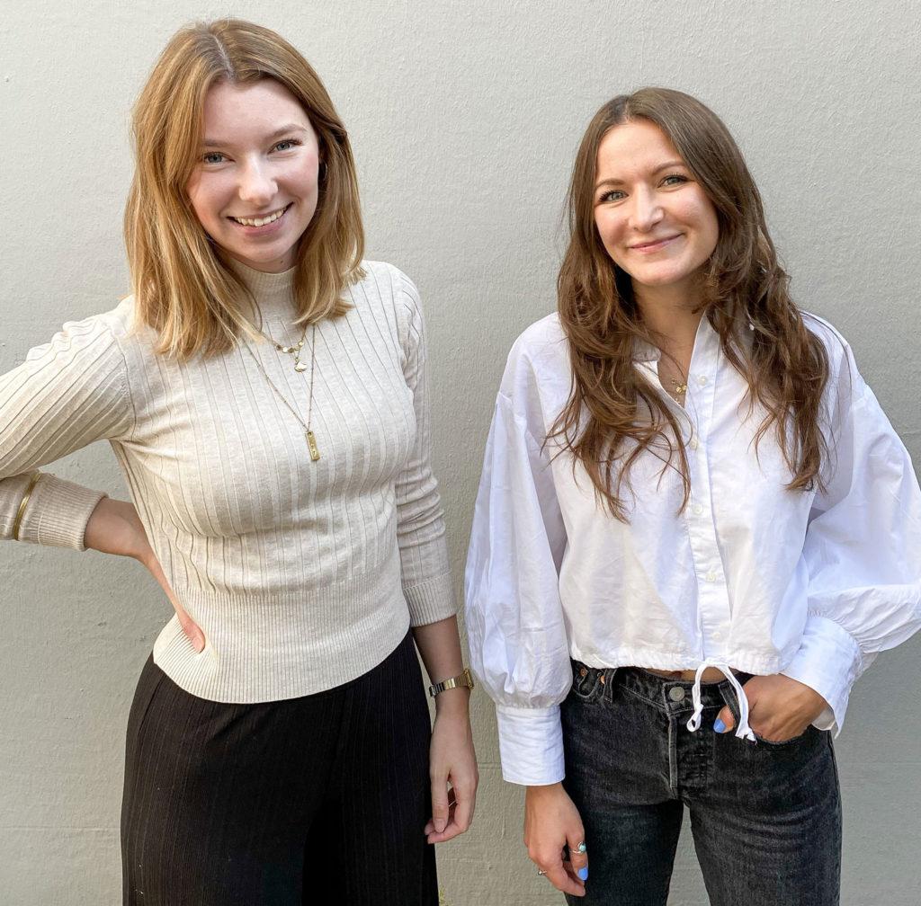 Elise und Lily tragen beide weiße Oberteile. Sie stehen vor einer weißen Wand und lächeln in die Kamera.