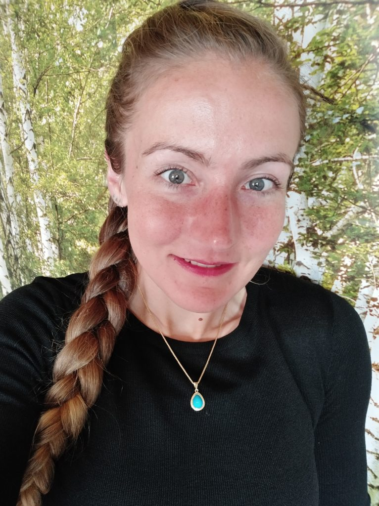 Lisa steht vor einem Birkenwald. Sie trägt ihre langen blonden Haare zu einem geflochtenen Zopf über die Schulter.