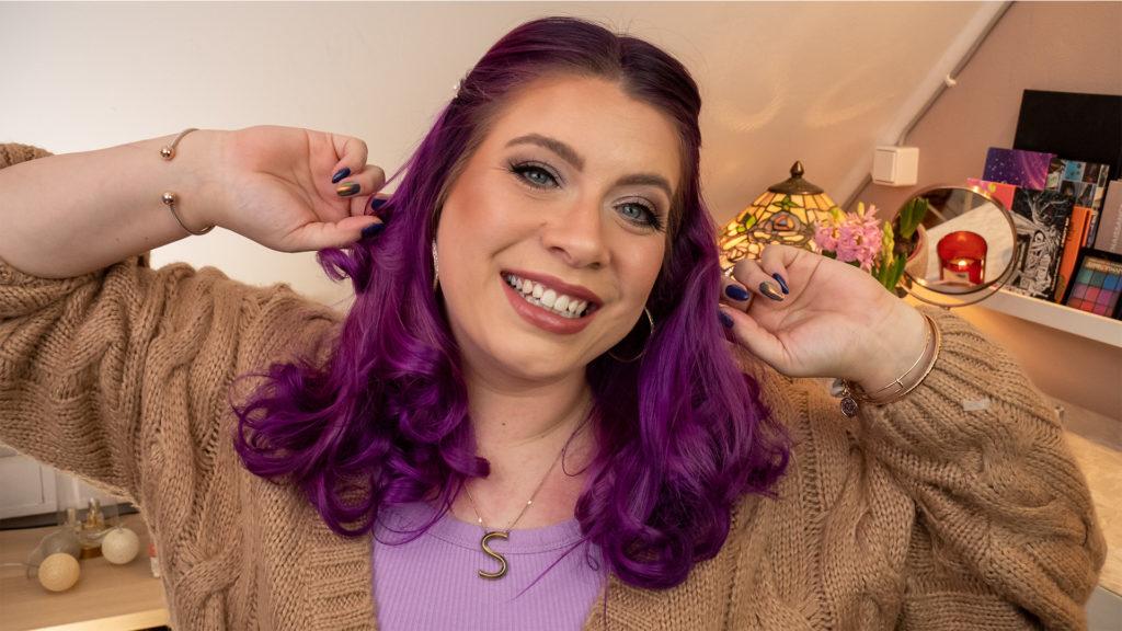 Sara hat ihre violetten Haare zu Locke frisiert. Sie lächelt in die Kamera und greift sich in die Harre.