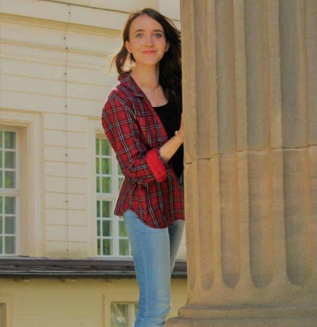 Die brünette Katharina beugt sich lächelnd um eine große Säule herum Richtung Kamera. Sie trägt eine hellblaue Jeans und ein rotes Karohemd.