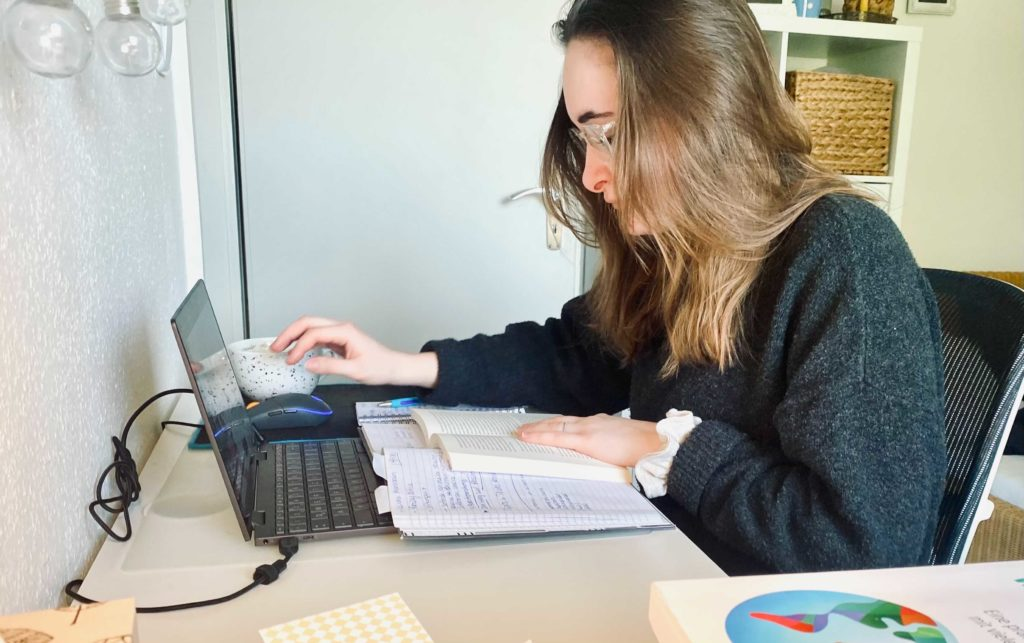 Annina sitzt an ihrem Schreibtisch. Der Laptop steht aufgeklappt auf dem Tisch. Vor ihr liegen Bücher und Aufschriebe.