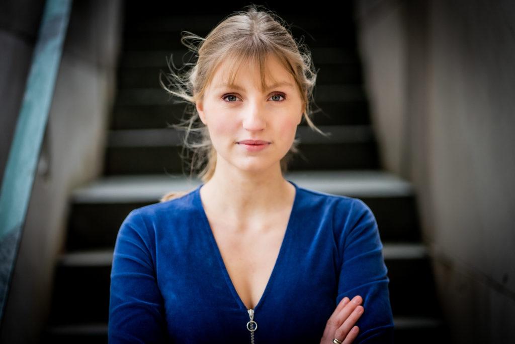 Die blonde Annalisa trägt ein blaues Oberteil und hat die Arme vor der Brust verschränkt. Sie steht vir einer großen grauen Treppe.