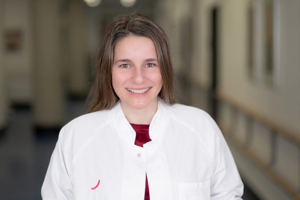 Dr. Mandy Mangler trägt einen weißen Ärztinnenkittel über einem roten Pullover. Sie steht auf einem Krankenhausflur und lächelt in die Kamera.