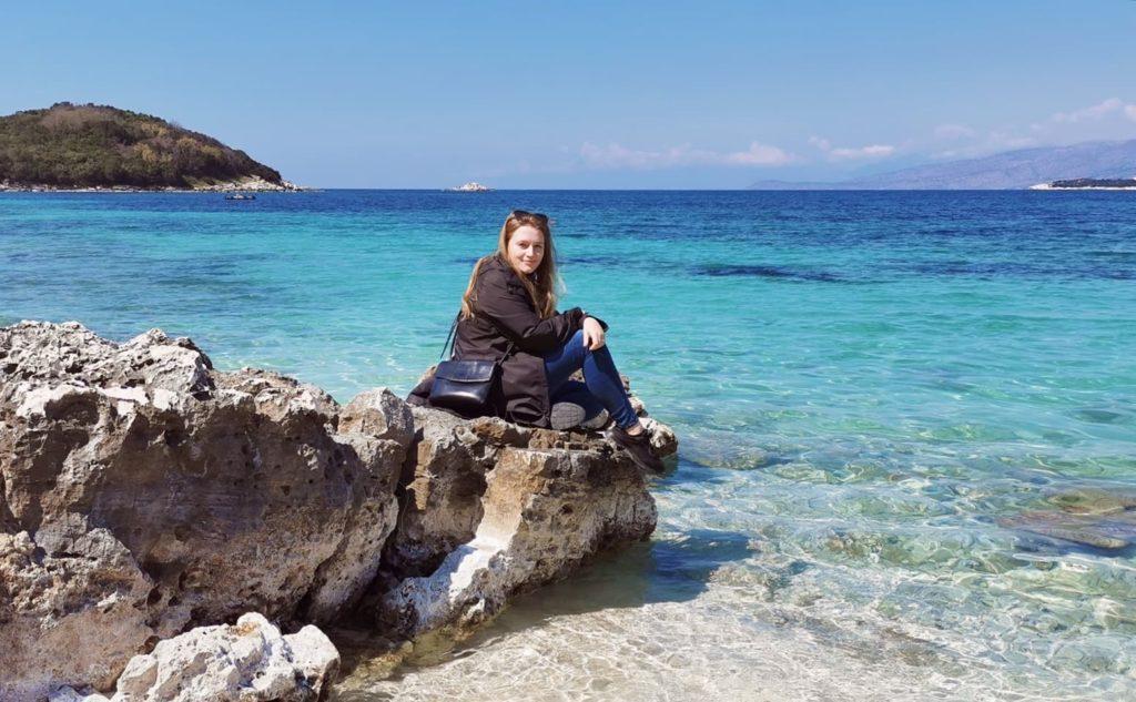 Josephine sitzt auf einem Fels am Meeresufer und blickt in die Kamera