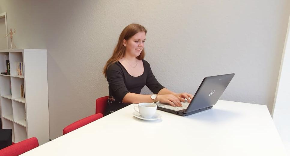 Emely trägt ein schwarzes Oberteil und sitzt in einem Büro an ihrem Laptop. Neben ihr steht eine Tasse und hinter ihr ein Regal.