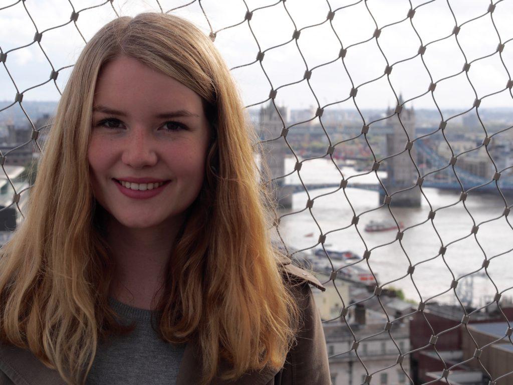 Lea steht auf einer Brücke. Im Hintergrund sieht man die London Tower Bridge. Sie lächelt in die Kamera