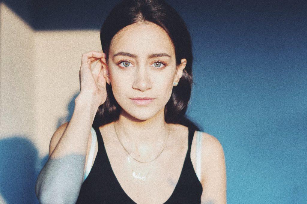 Helen Fares sitzt vor einer sonnenbeschienenen Wand. Sie trägt ihre dunklen Haare offen und streicht sie mit der rechten Hand hinters Ohr