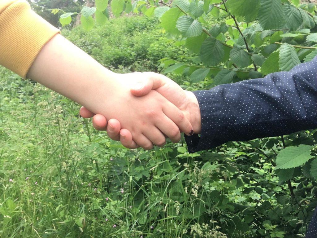 Zwei Hände schütteln sich. Im Hintergrund sieht man Büsche und Wiese.