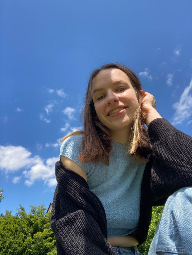 Charlotte sitzt auf einer Wiese. Hinter ihr sieht man den blauen Himmel und eine Reihe Büsche. Sie trägt ihre braunen Haare offen und hat ihren Kopf auf ihre Hand gestützt