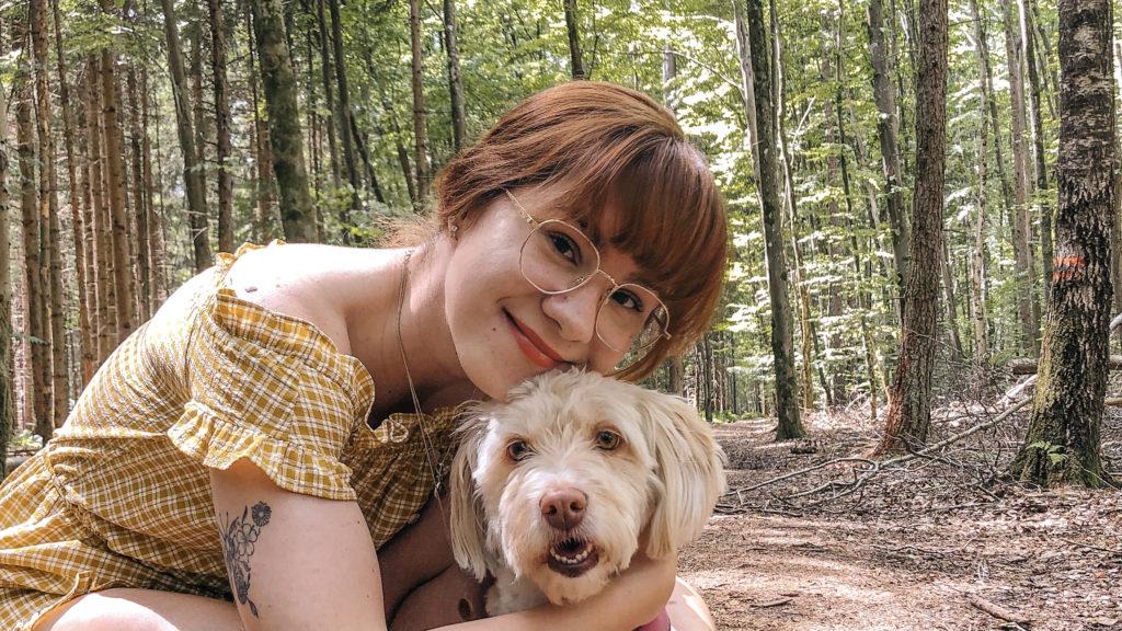 Julia kniet auf einem Waldweg und hat die Hände um den Hals ihres weißen Hundes gelegt