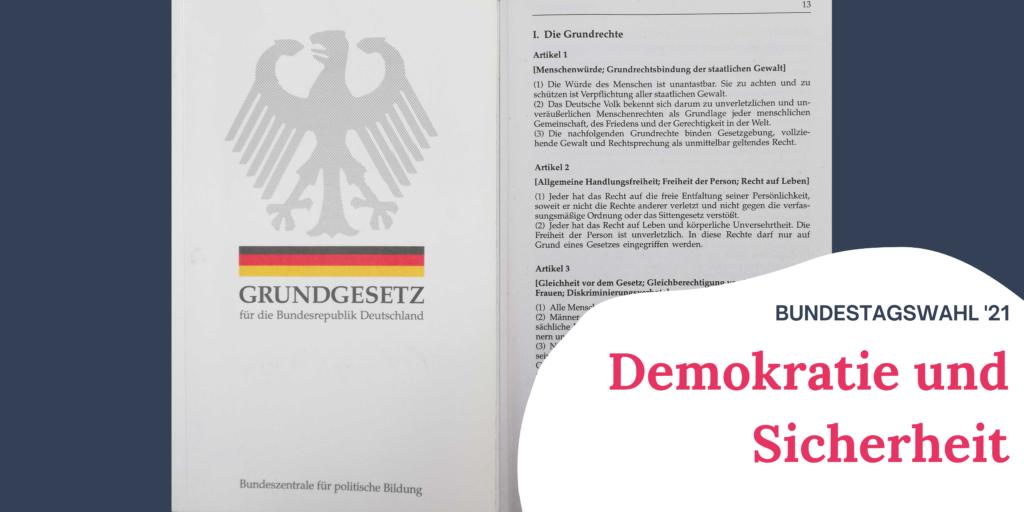 """Auf dem Bild sieht man das Cover des Grundgesetztes und die erste Seite, auf der die Grundrechte aufgeschrieben sind. Rechts im Bild steht """"Bundestagswahl '21 Demokratie und Sicherheit"""""""