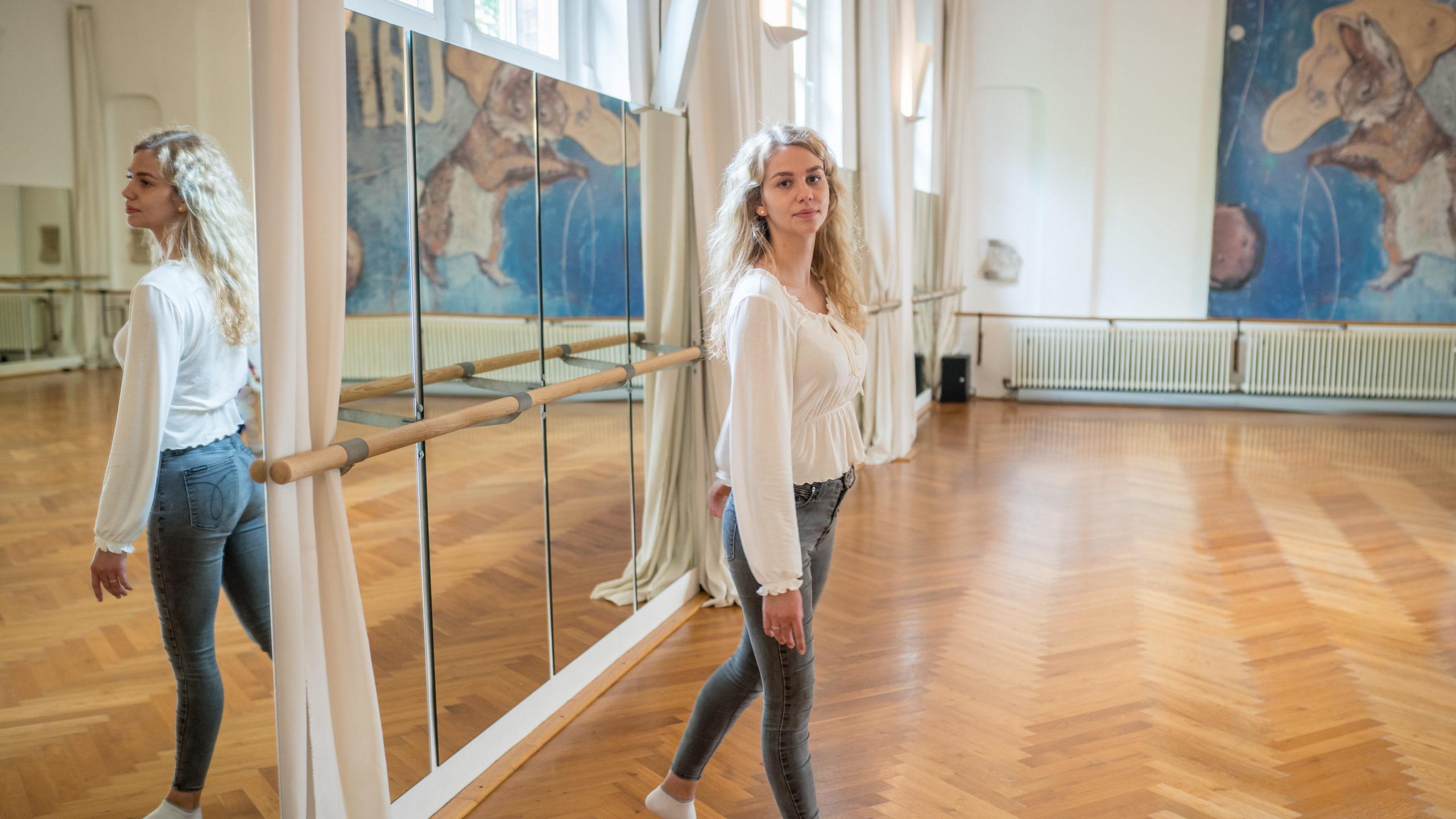 Eine junge Frau steht in einem Ballettsaal. Sie trägt eine weiße Bluse und eine blaue Jeans. Hinter ihr ist ein Spiegel angebracht, in dem sie sich spiegelt.